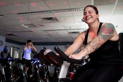 A spin instructor motivates her spin class students.