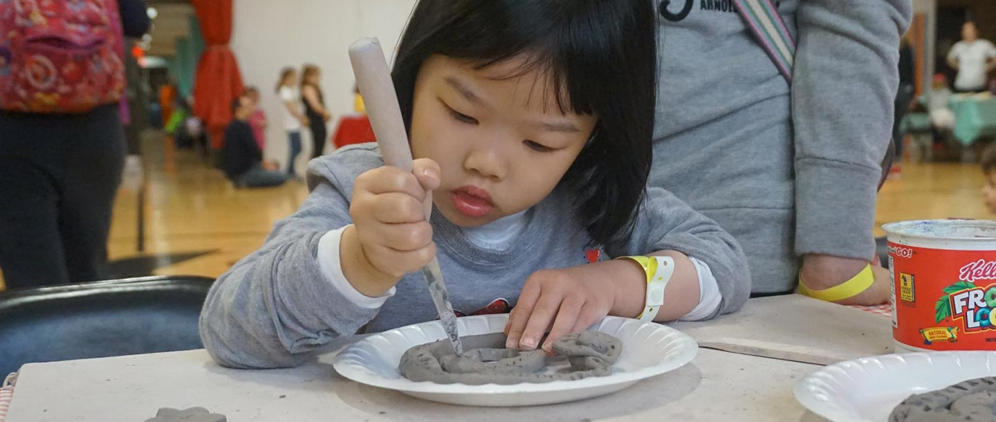 Young girl sculpts clay for art project