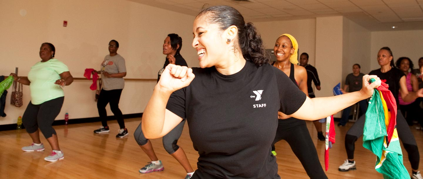 A instructor leads a YMCA group fitness dance class.