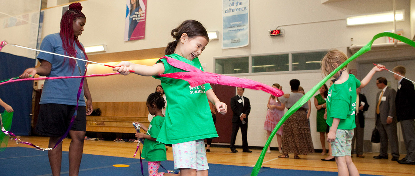 Young girl does gymnastics at summer day camp at YMCA in Manhattan