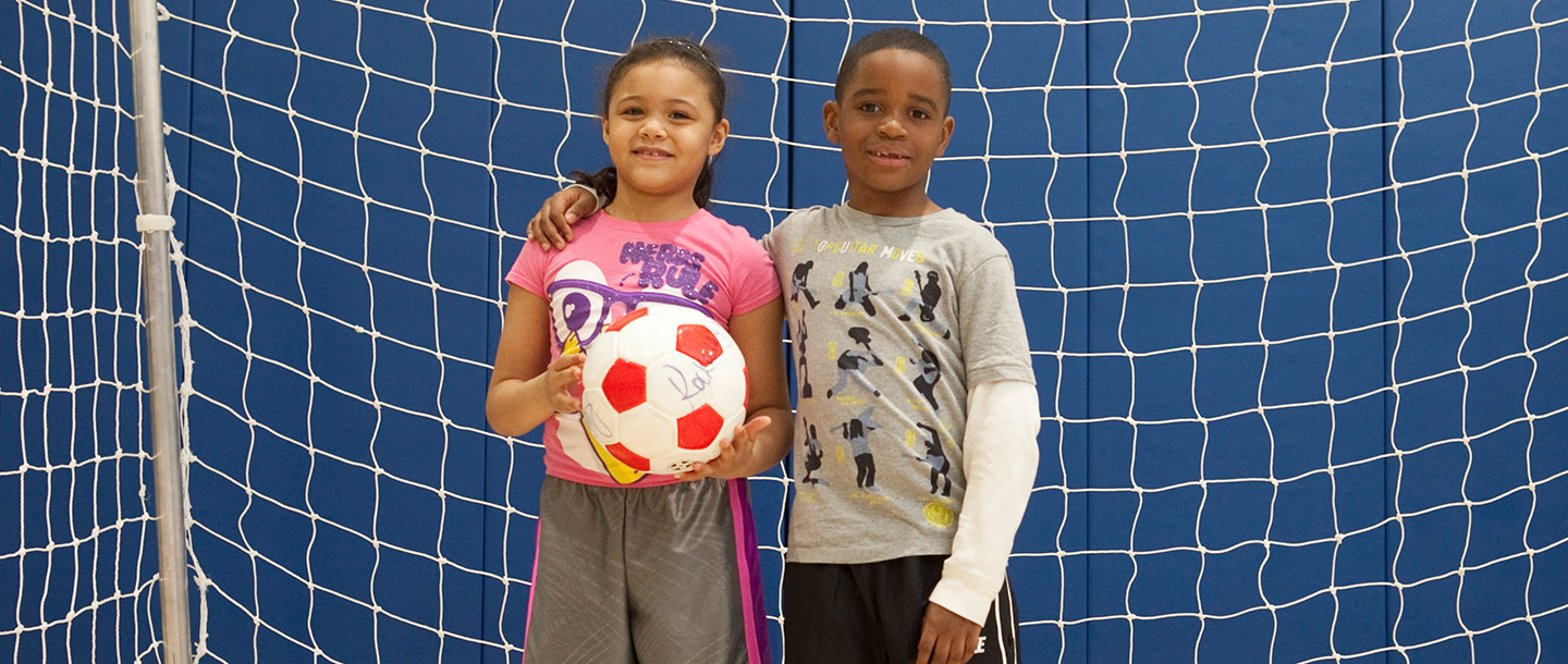 Girl and boy playing soccer at the YMCA in Brooklyn