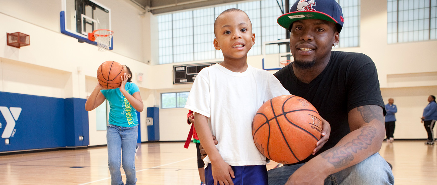 Father and son playing basketball at YMCA in Brooklyn