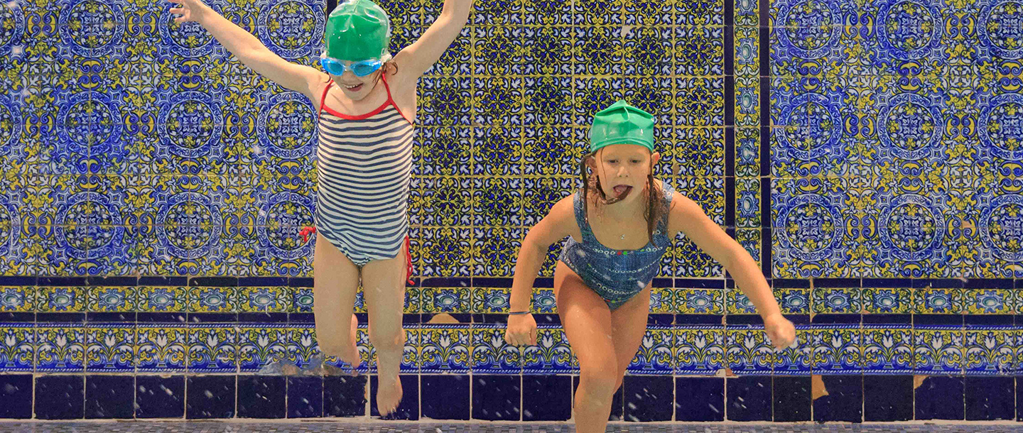 Two girls jump into the pool during a kids birthday party at the West Side YMCA.