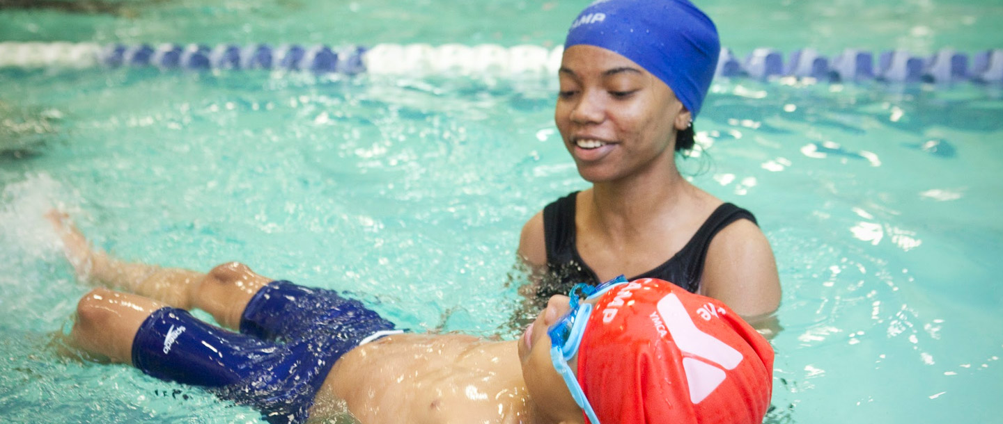 A YMCA camp counselor helps a child swim in the pool.