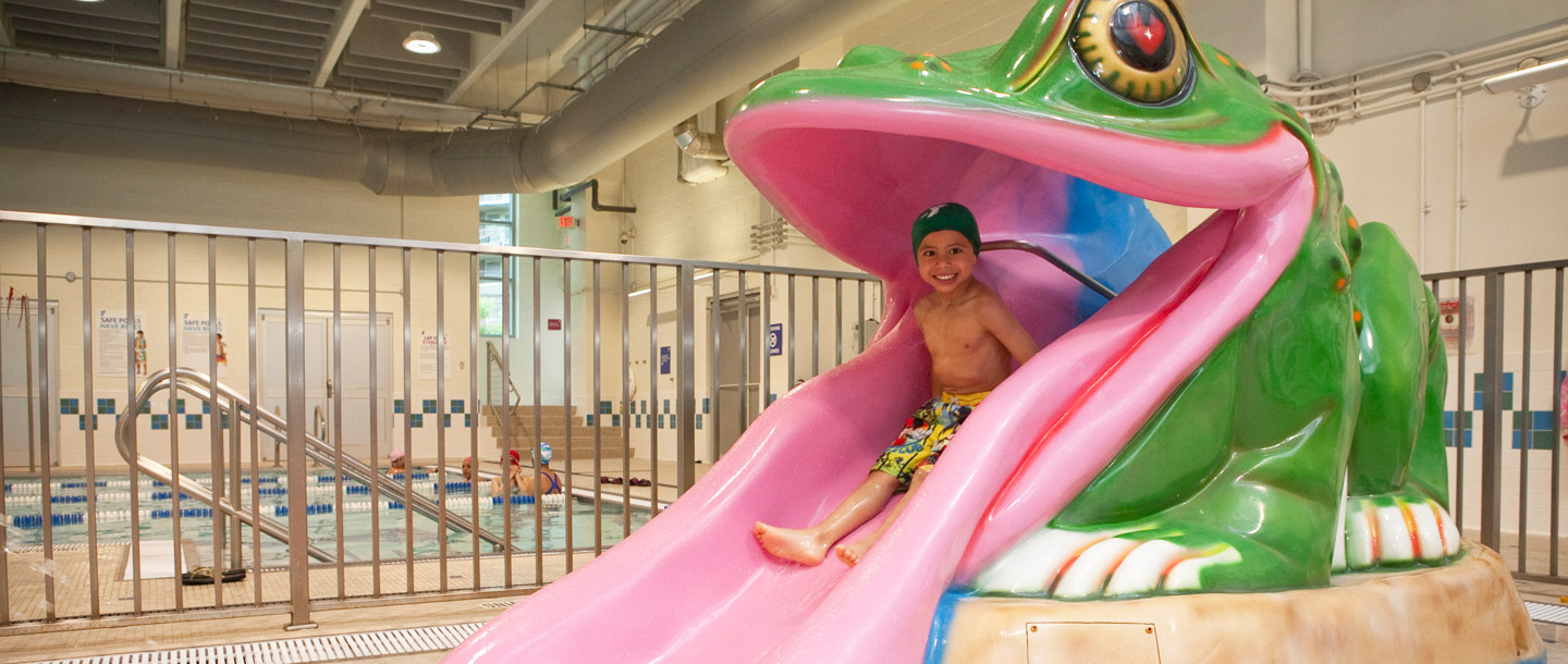 A child on a frog water slide at the Coney Island YMCA.