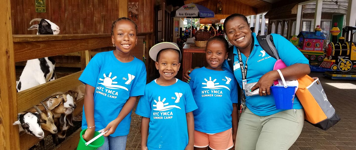 Three kids and a YMCA staff member at a YMCA summer day camp.