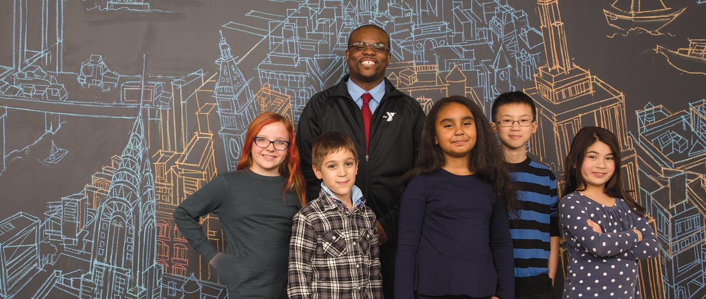 A group of kids and a Y staff member standing in front of a map of NYC.