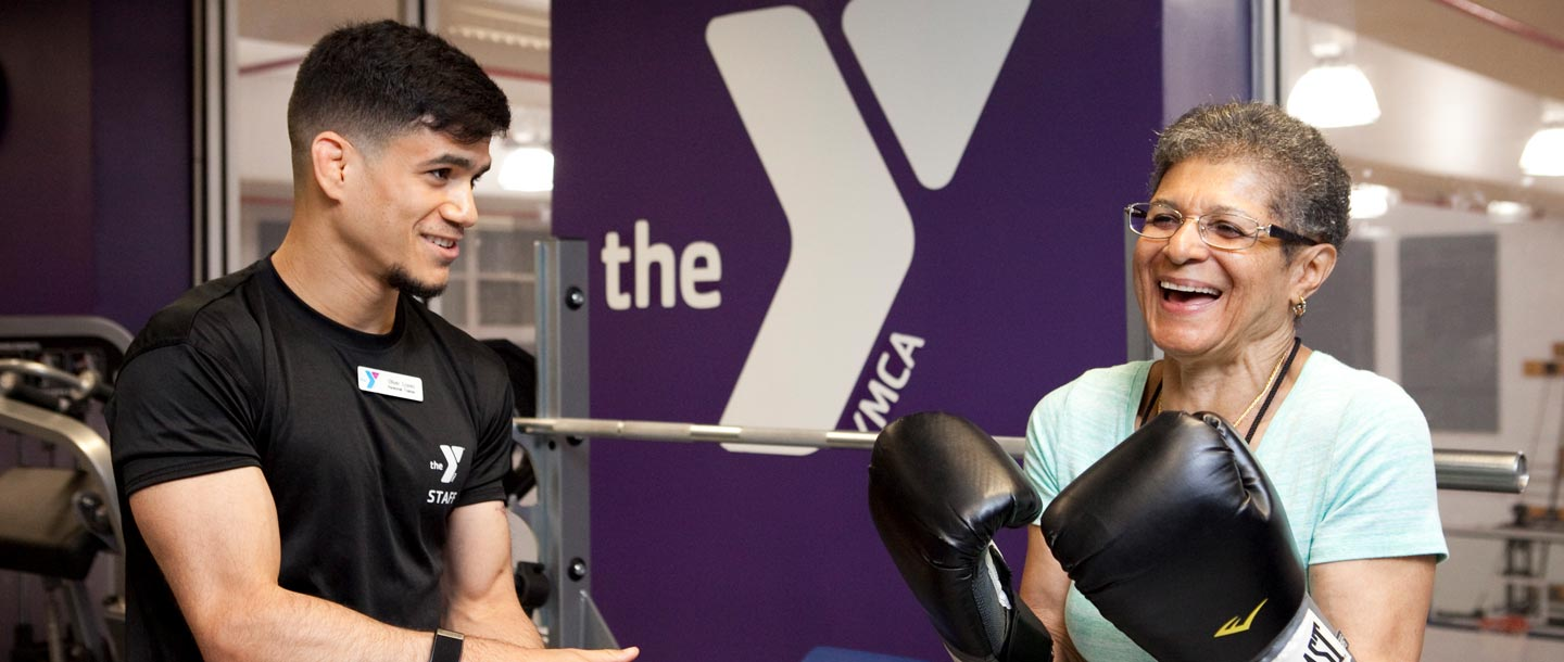 A member with boxing gloves works with a YMCA personal trainer.