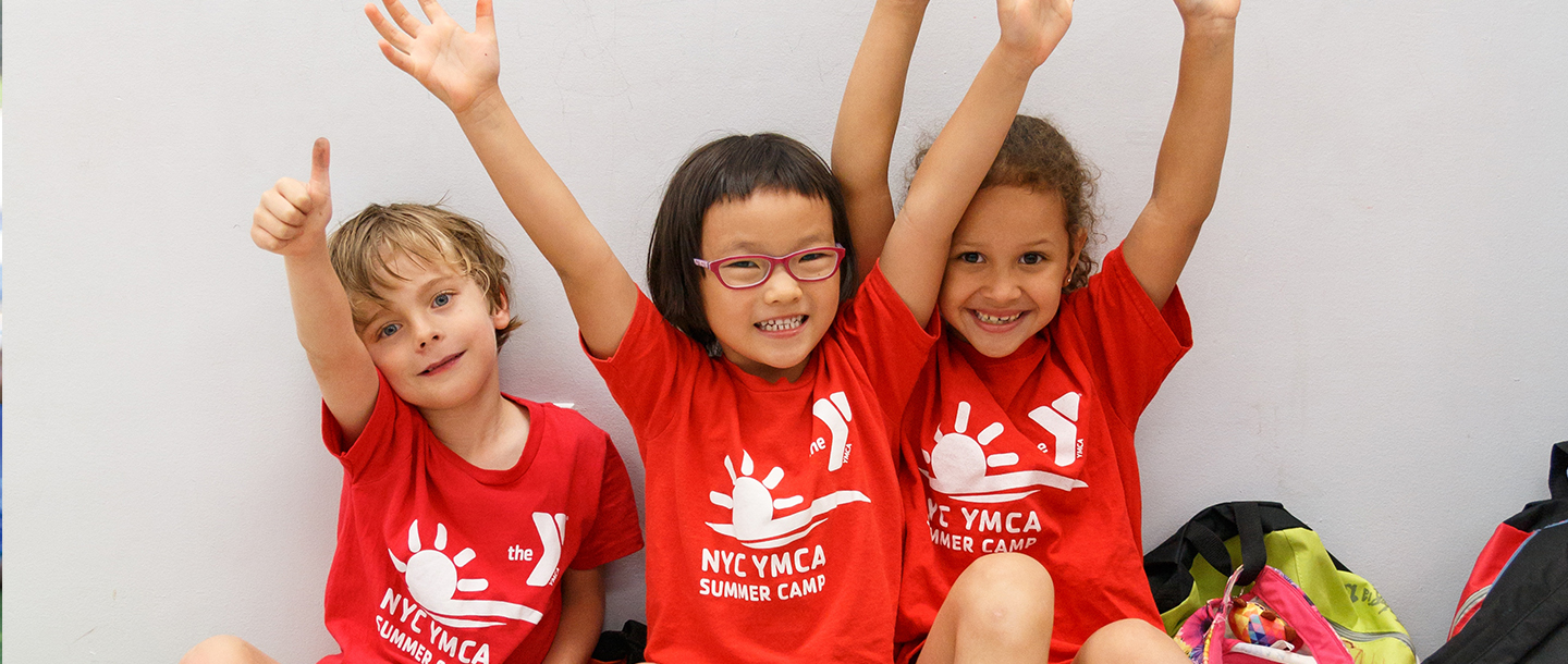 Three kids raise their arms happily at YMCA summer day camp.