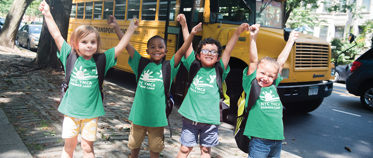 Four kids raise their hands up in the air wearing YMCA camp tee shirts.