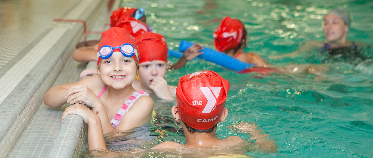 Kids swim in a pool at the YMCA summer day camp
