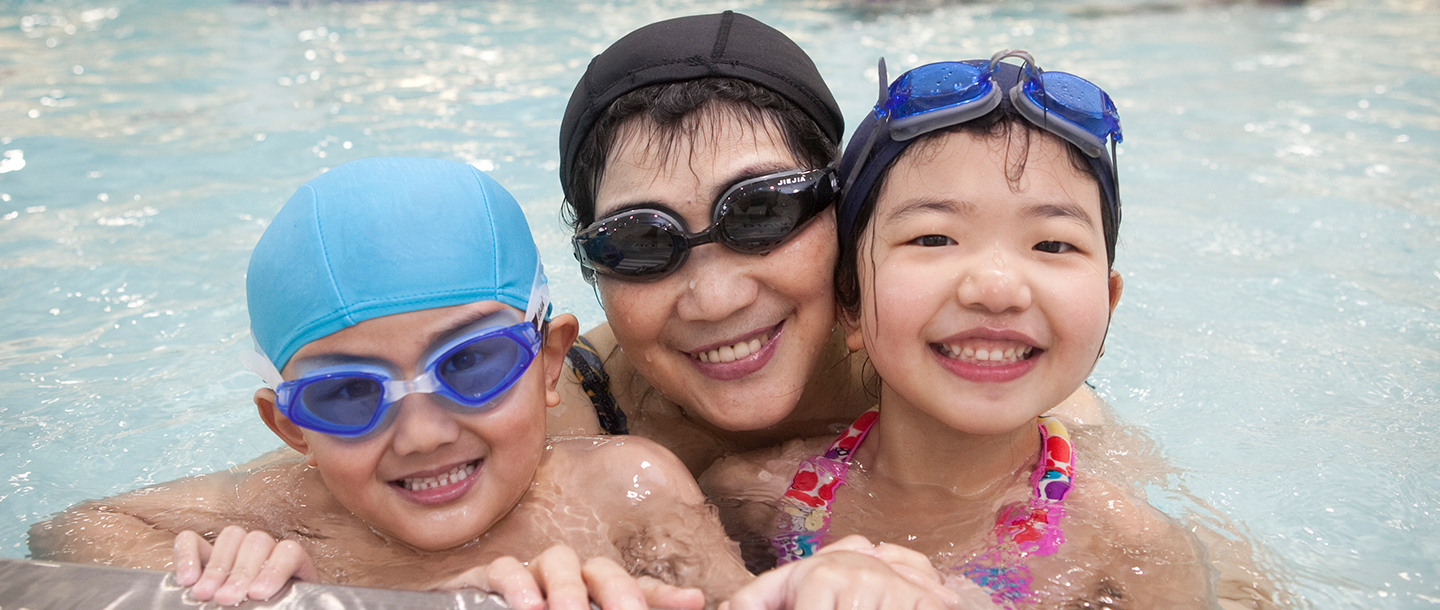 A mother and her two kids in the pool during a YMCA birthday party.