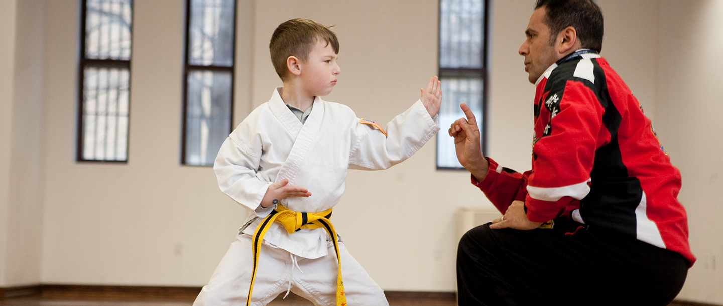 A child practices karate with a coach.