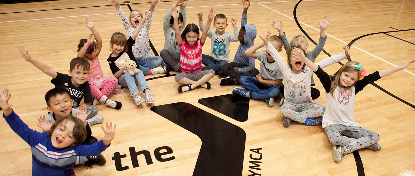 Kids wave from the YMCA gym.