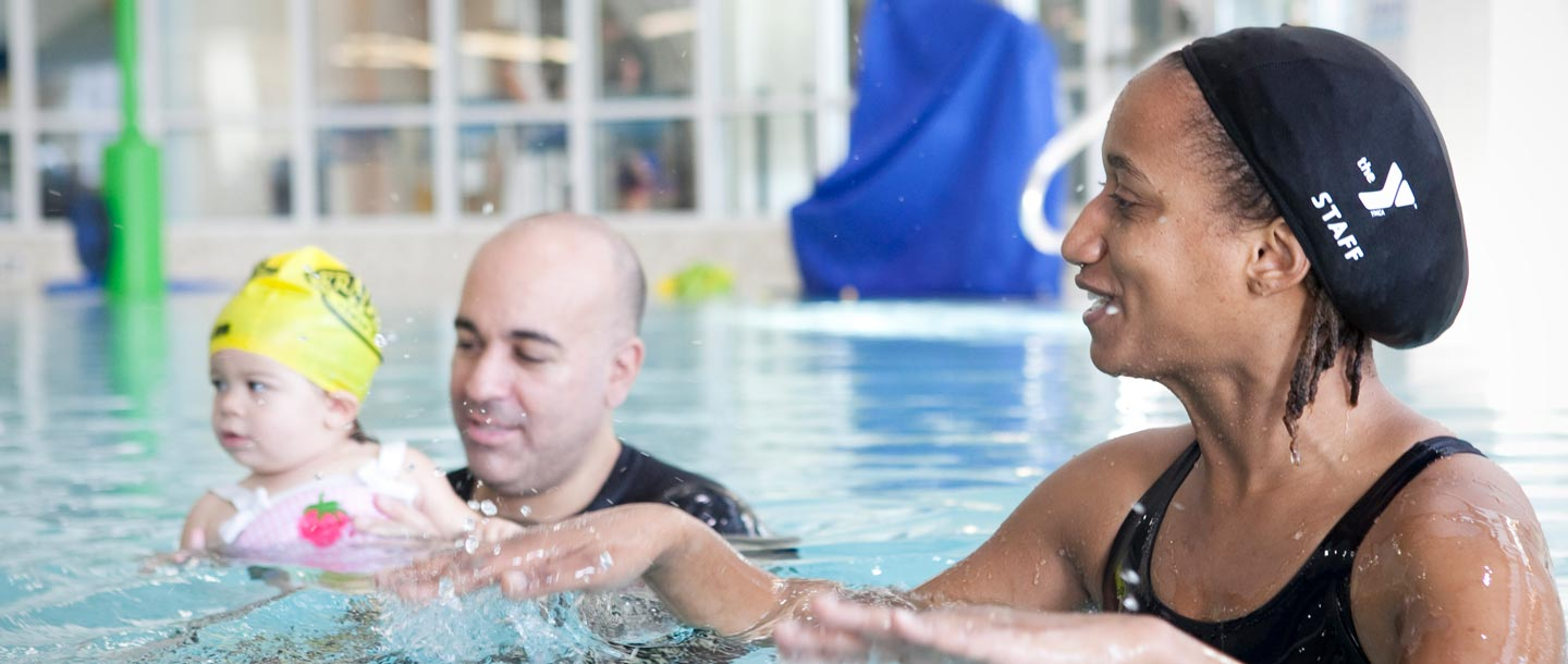 A YMCA teacher teaches a parent and baby swim lesson.