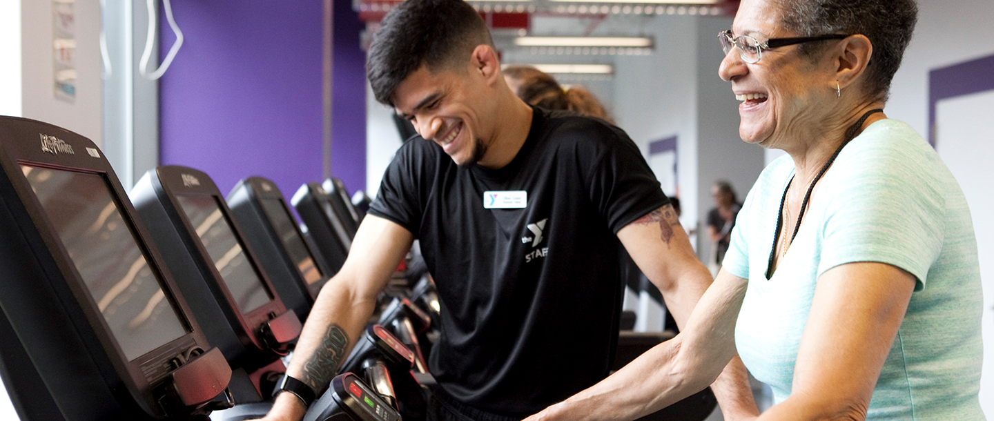 A personal trainer works with a YMCA member in the gym.