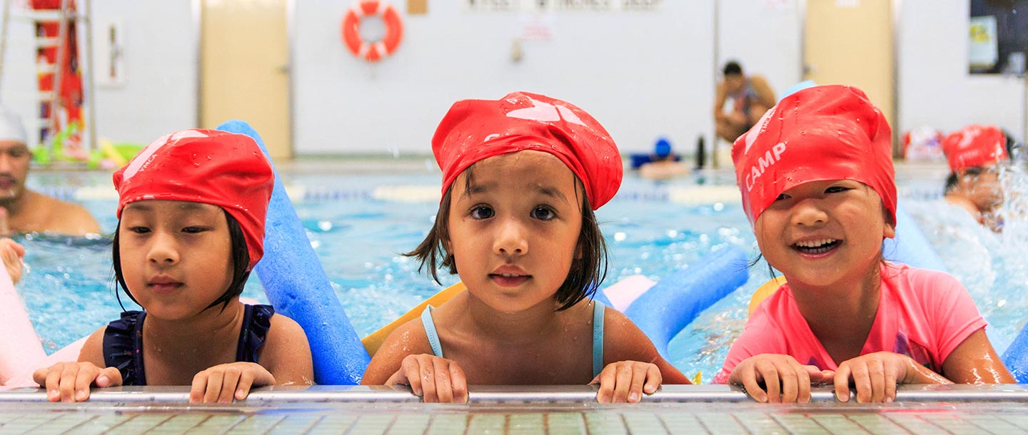 Three kids in a swimming class at the YMCA.