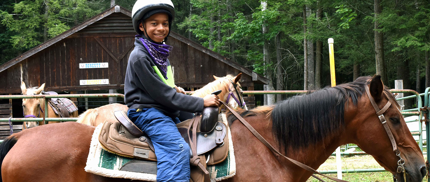 A child on a horse at YMCA overnight camp.