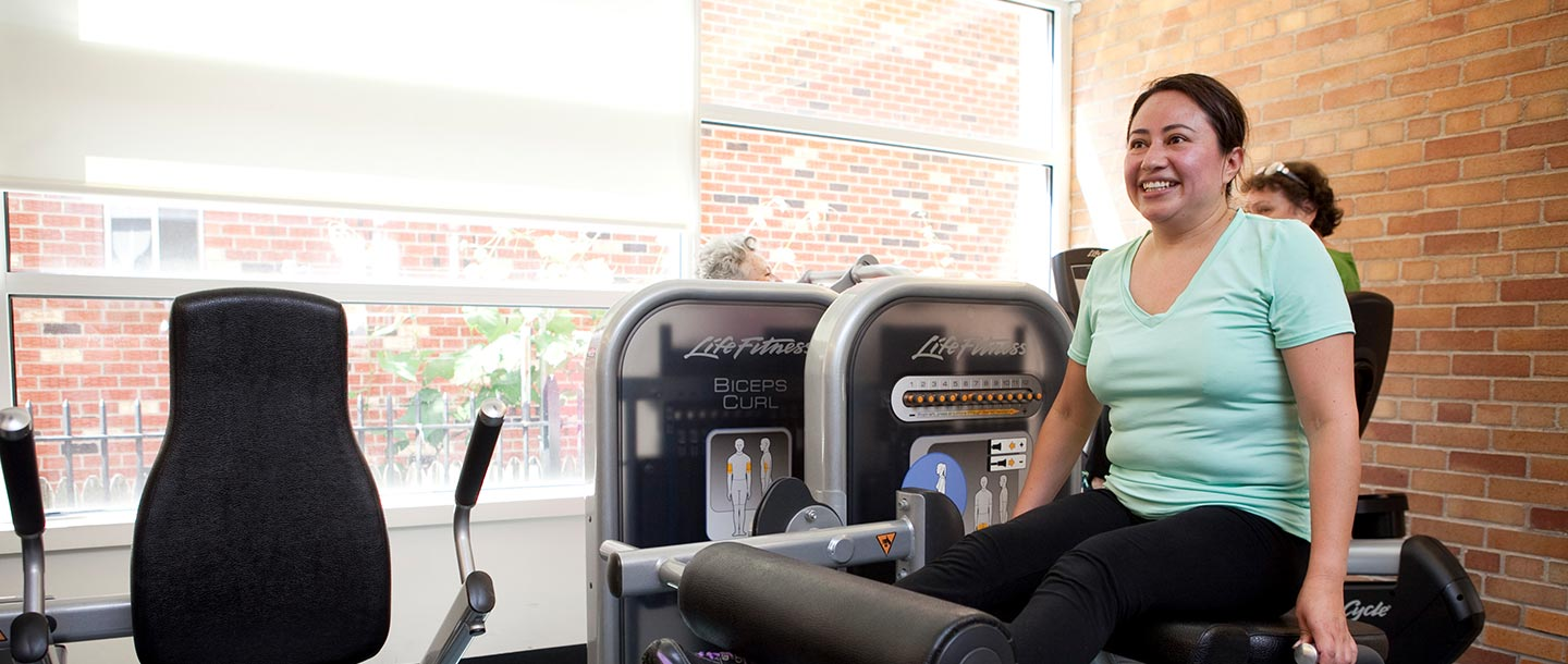 A woman works out in strength training equipment at the Ridgewood YMCA.