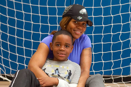 A mother and son in front of a soccer net.