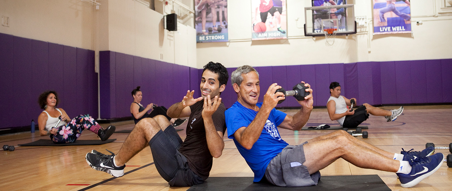 Partner work out in strength training fitness class at YMCA in Brooklyn.