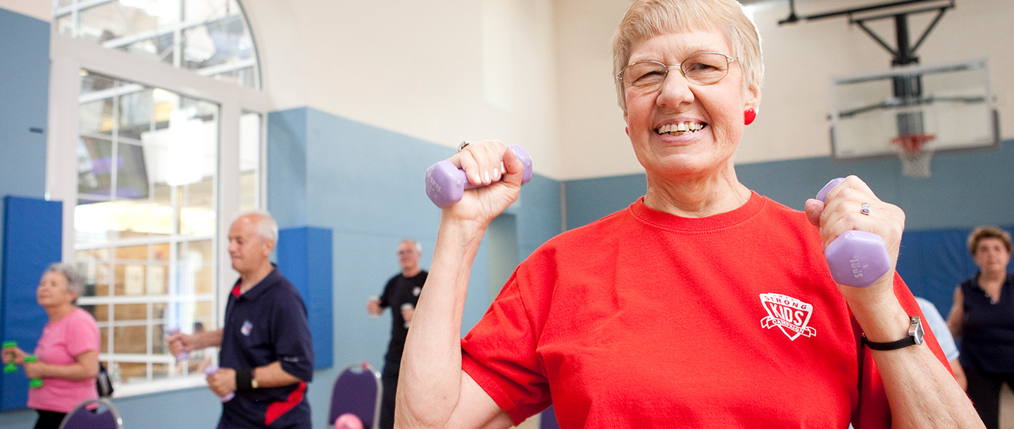 An active older adult works out in a group fitness class.