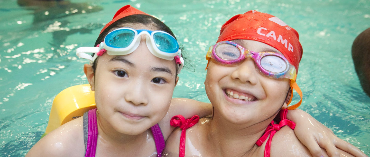 Two girls swimming in Vanderbilt indoor pool during YMCAc camp