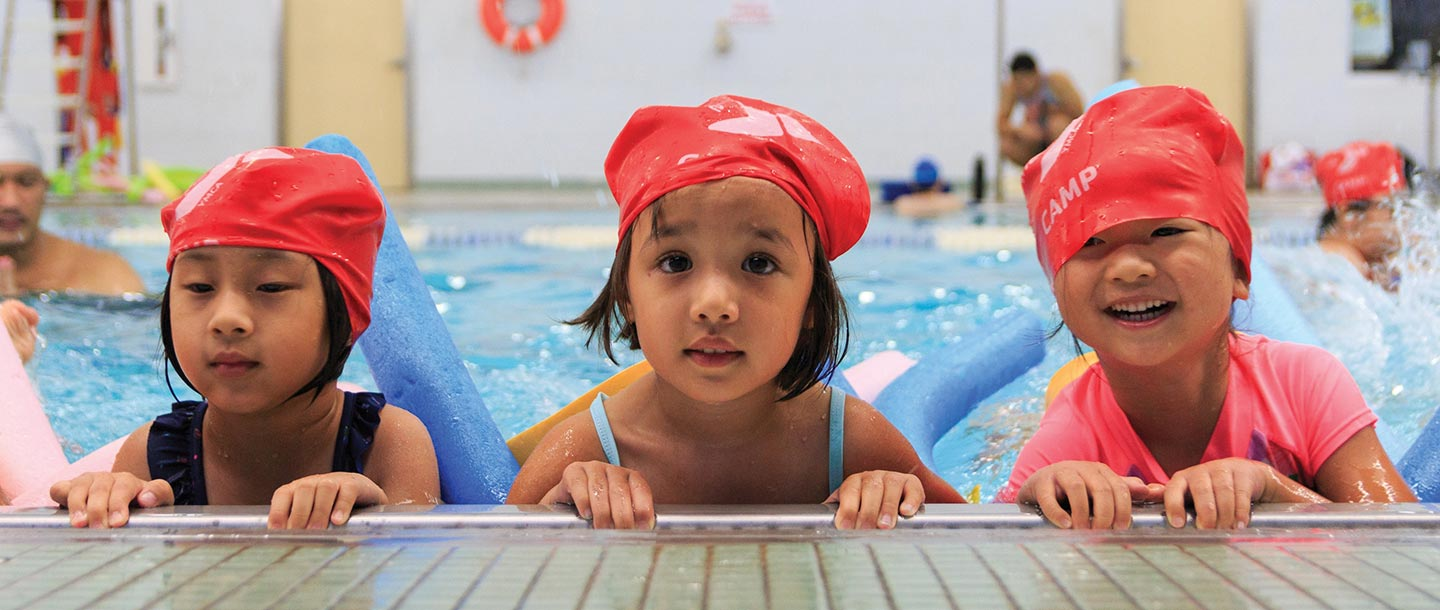 Three preschool girls swimming in LIC YMCA indoor pool during summer camp