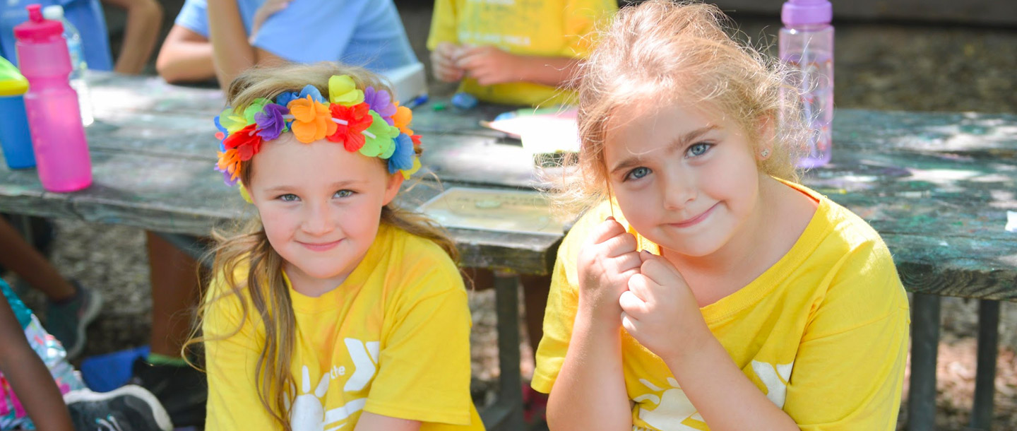 Two girls outside one with flower crown during YMCA summer camp.