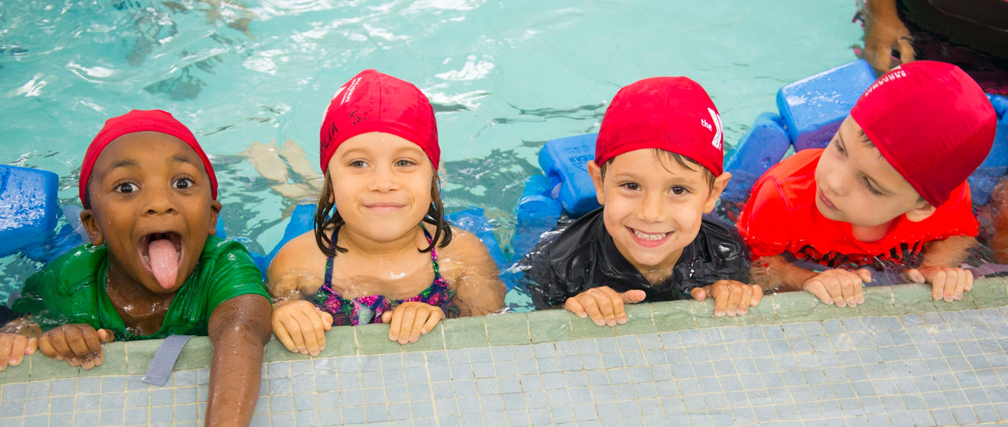 Group of preschool campers learning how to swim at indoor YMCA pool during summer camp