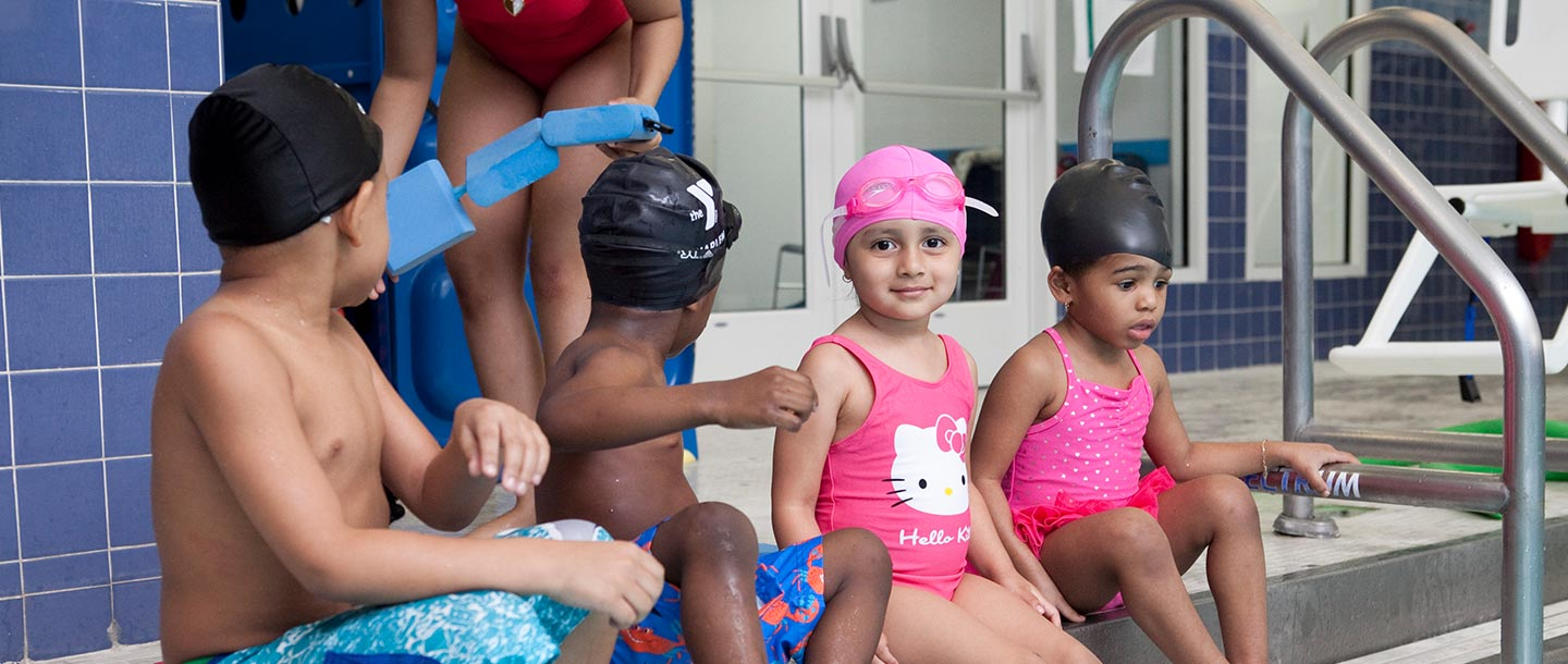 Preschool swim class sits on stairs of indoor pool at the YMCA