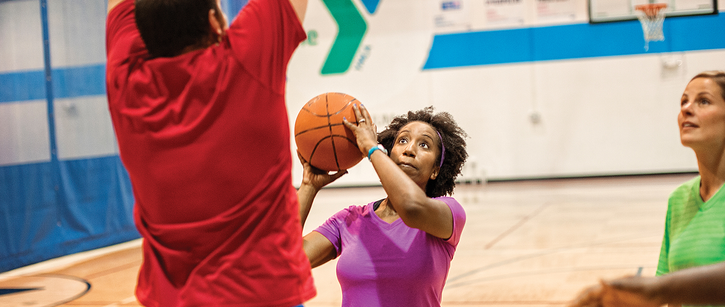 Group of adults playing basketball indoors at YMCA