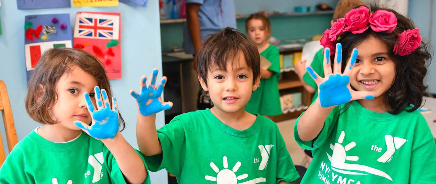 Three kids at McBurney summer camp with painted hands
