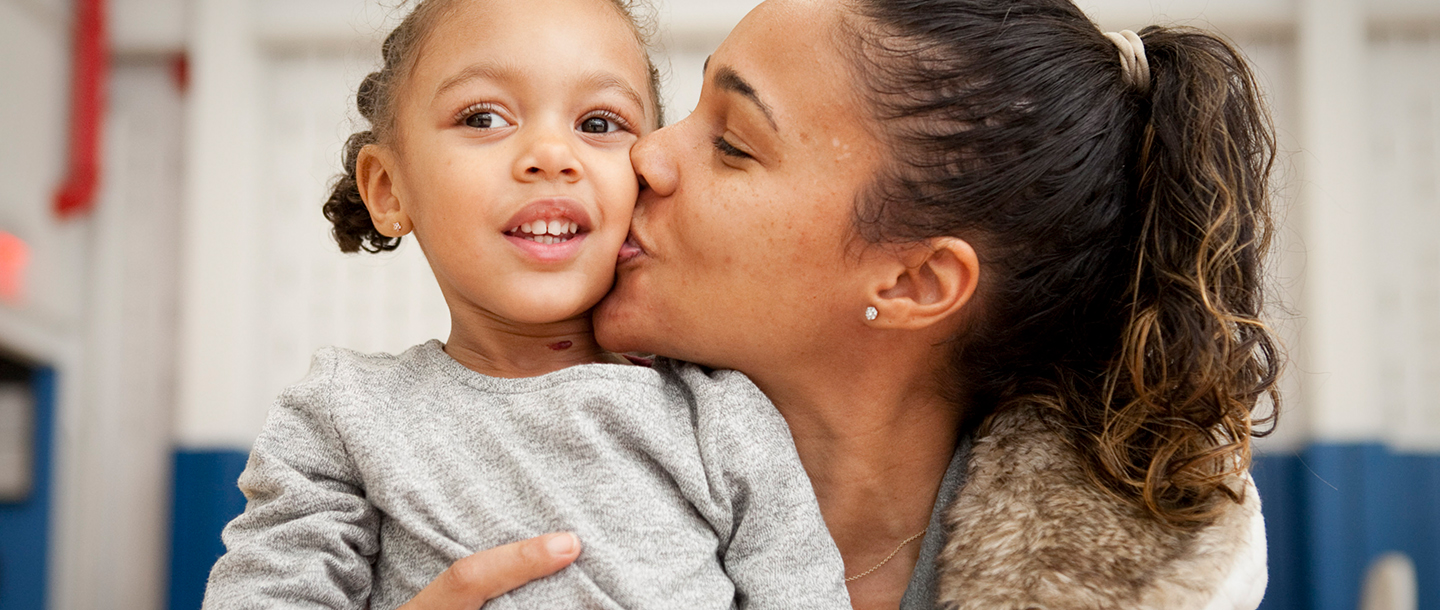 Mom kissing daughter's cheek at YMCA