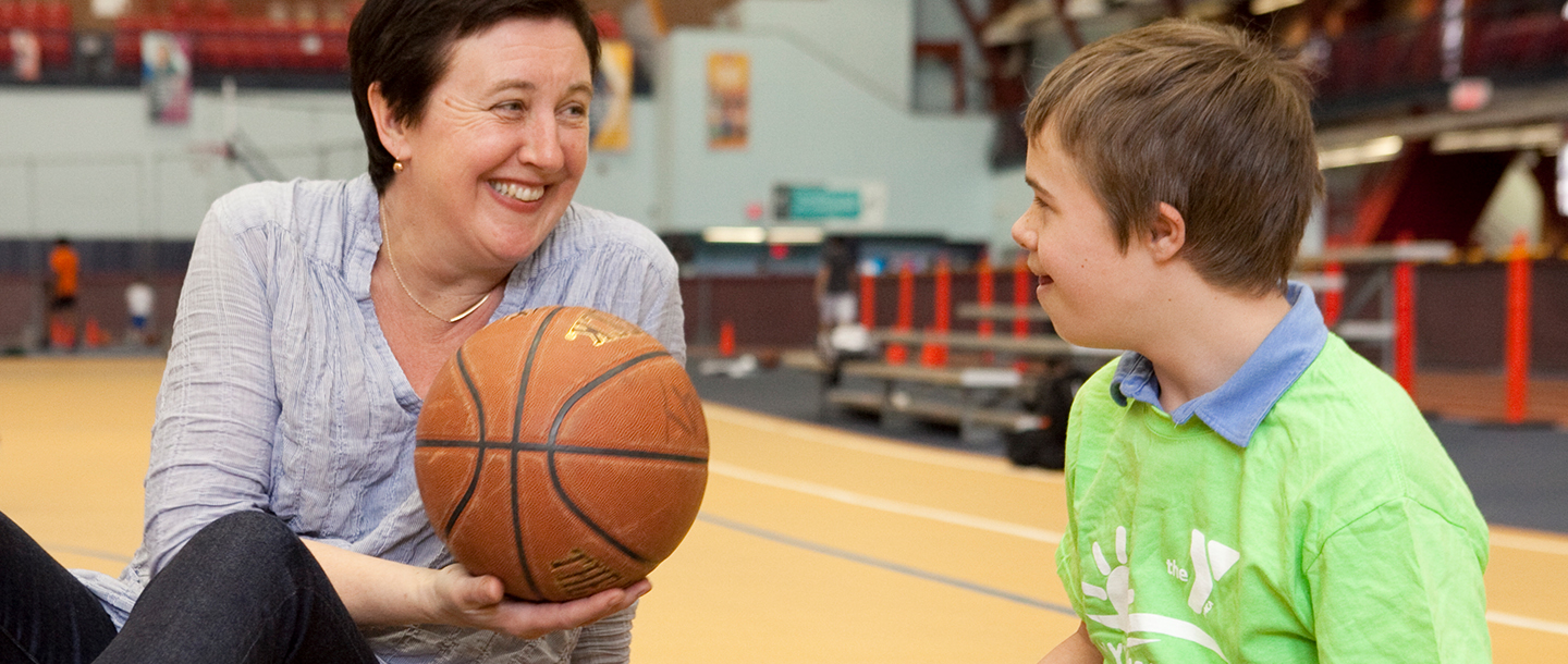 Mother and son playing basketball at the Park Slope Armory YMCA indoor gymnasium