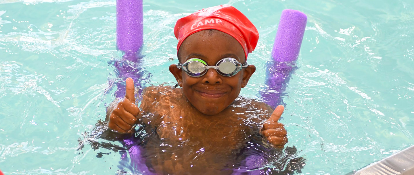 Summer camper swimming in indoor YMCA pool on noodle gives thumbs up
