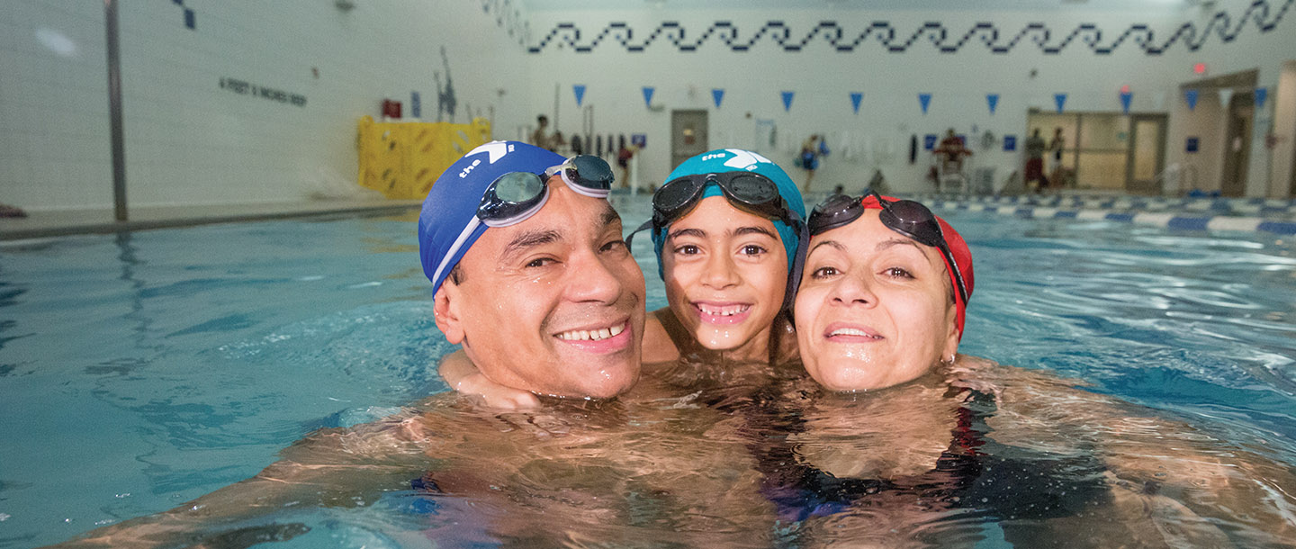 Dad, son, and mom swim together at YMCA indoor pool in Brooklyn