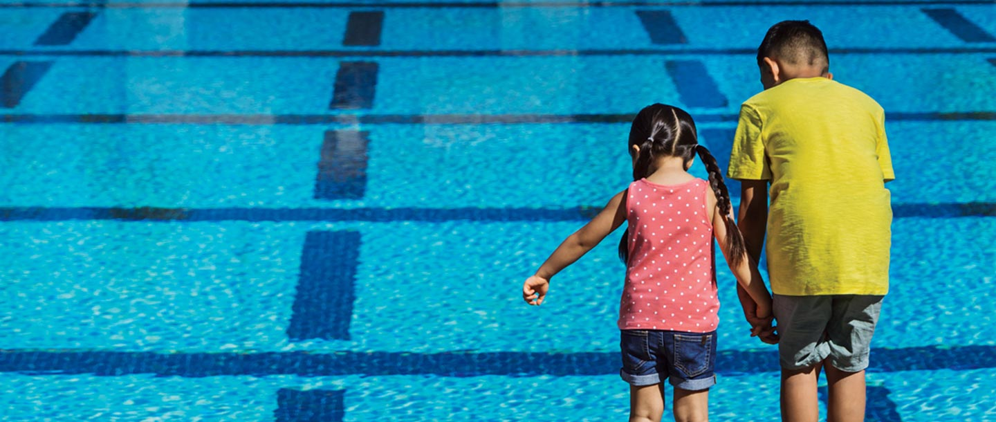 Two kids looking into a pool.