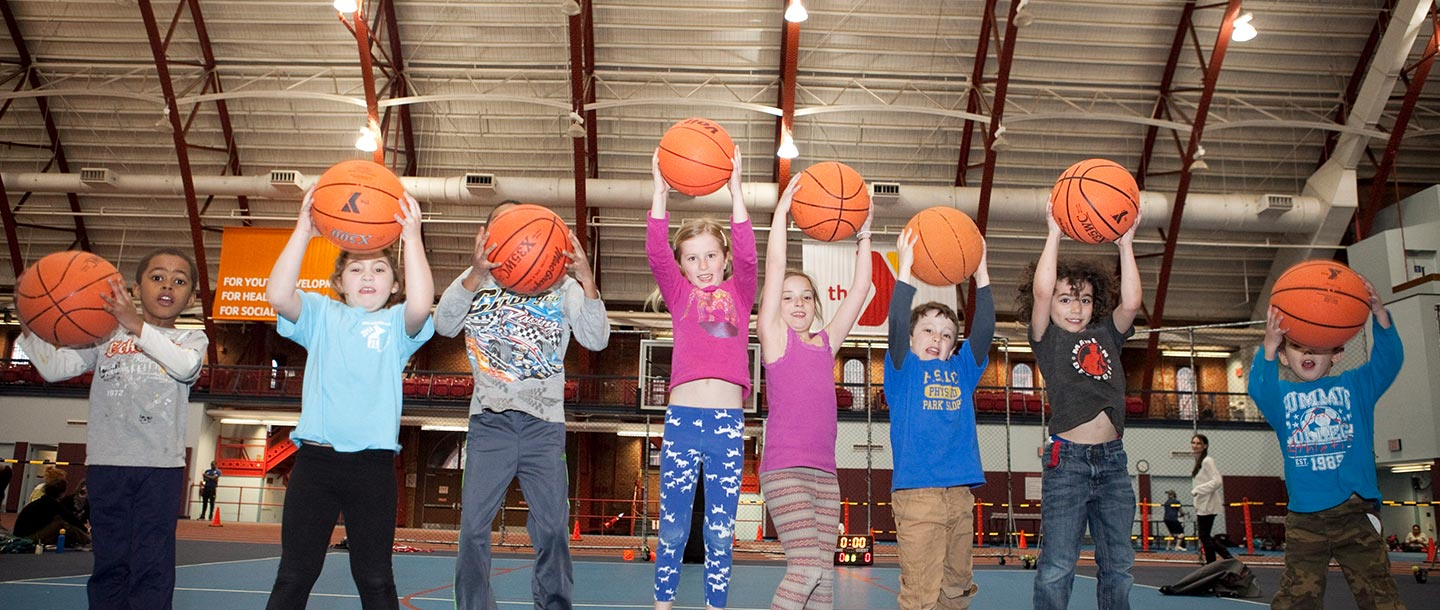 Kids jumping with basketballs in their hands at the Park Slope Armory YMCA