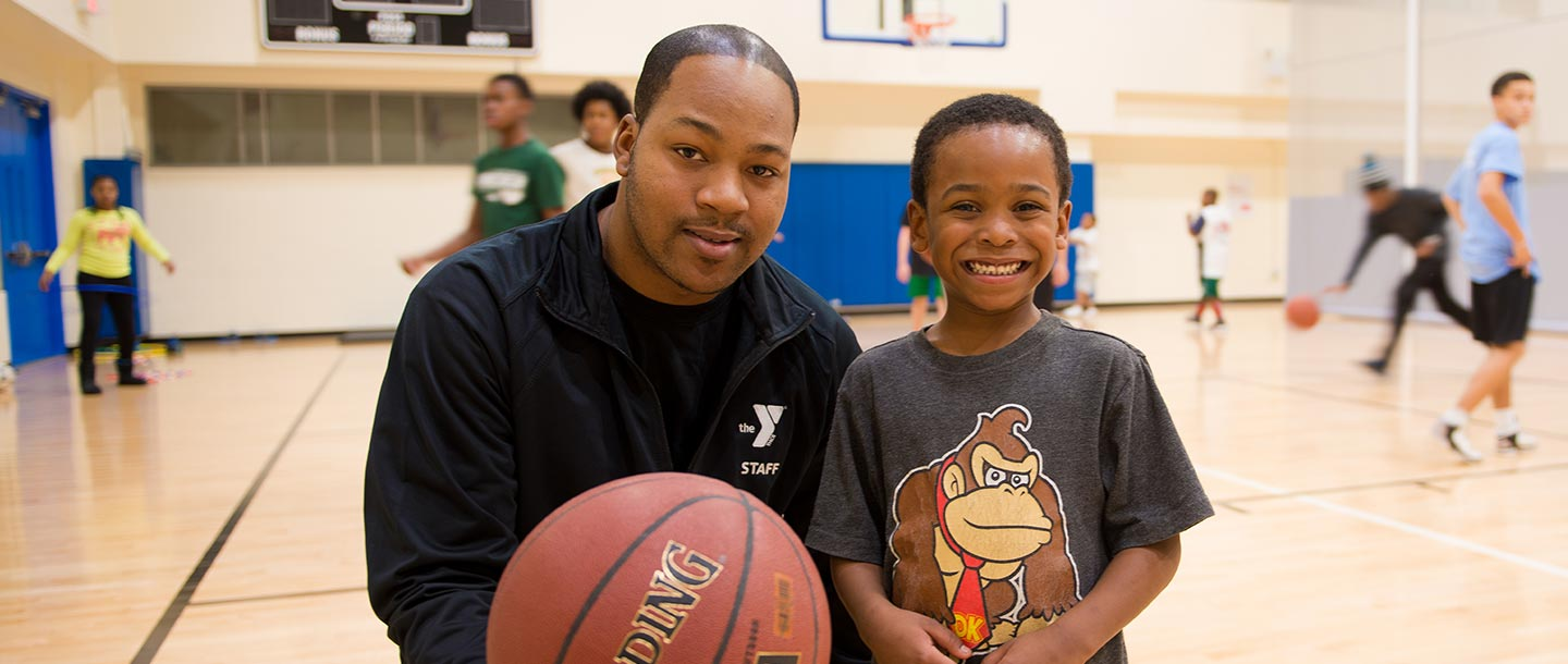 Young boy with YMCA basketball instructor at indoor court