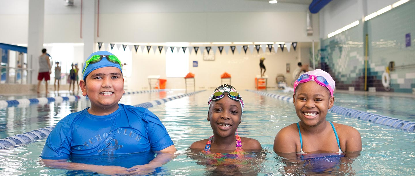 Three kids learning to swim in lap lane of indoor YMCA pool