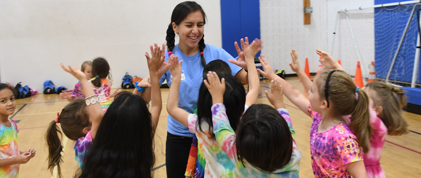 Camp counselor high fiving group of children at LIC YMCA gym