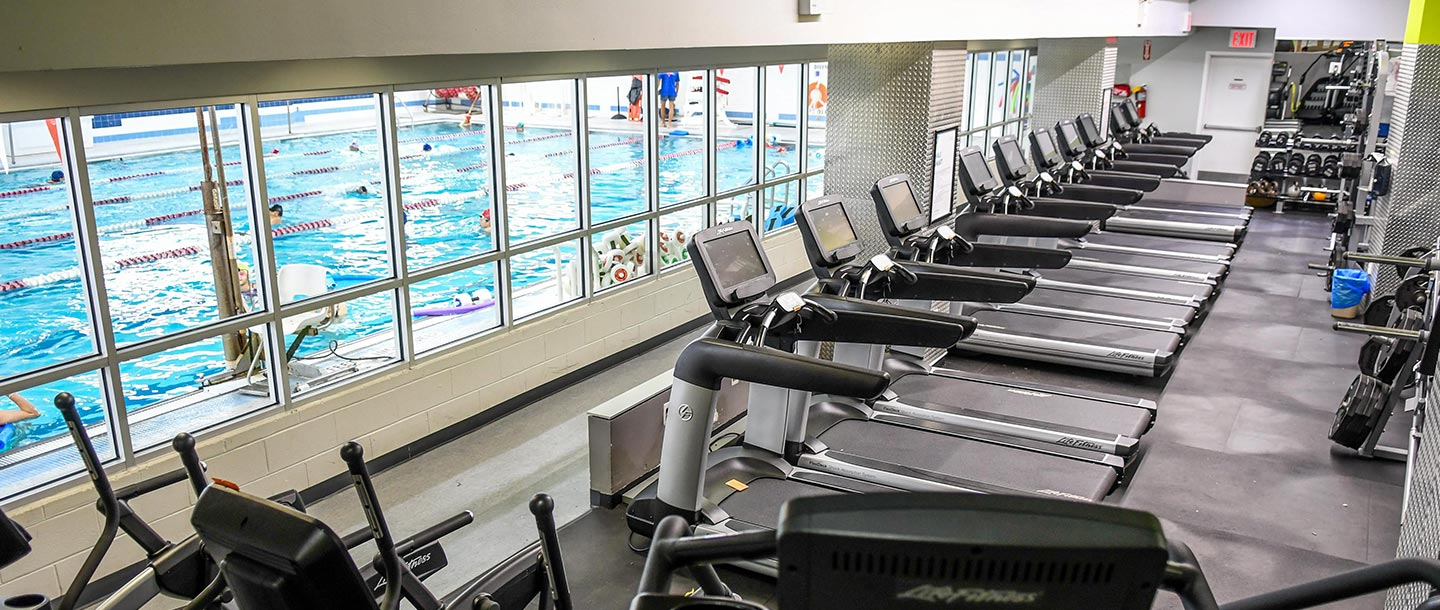 Chinatown YMCA fitness equipment treadmills with view of indoor pool