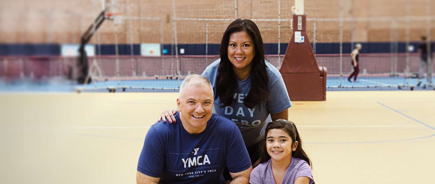 Family of dad, daughter, and mom together at Park Slope Armory YMCA basketball court