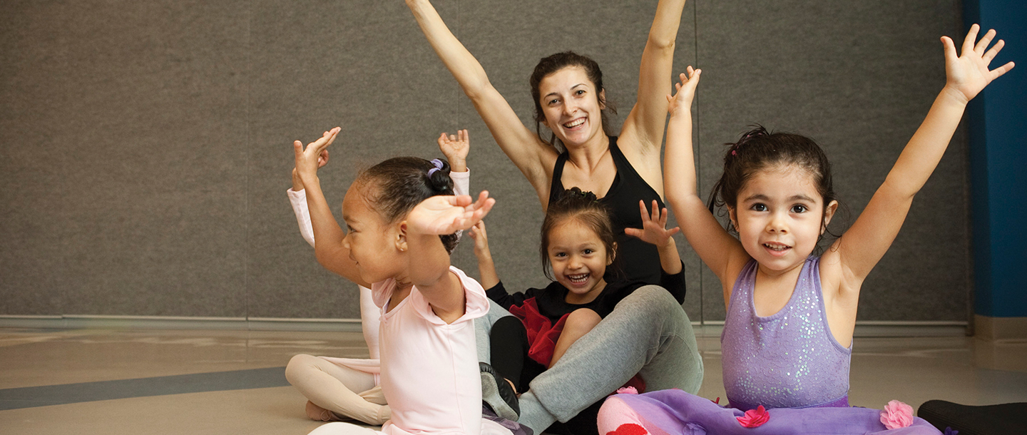 Three ballerina girls with YMCA instructor and arms up