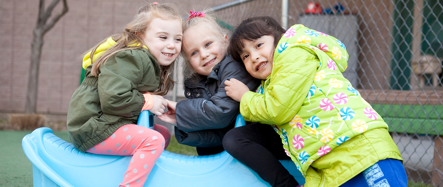 Three preschool girls playing outside at Staten Island YMCA playground for UPK