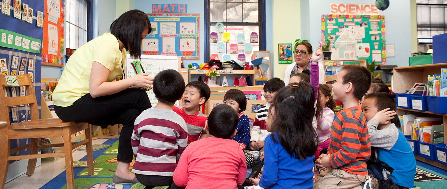 Teacher reads book to class of preschoolers sitting on floor of Flushing YMCA UPK classroom