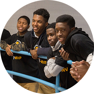 Group of teen boys holding railing of Bedstuy YMCA indoor basketball court