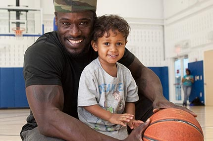 Dad with toddler son and basketball in Rockaway YMCA gymnasium
