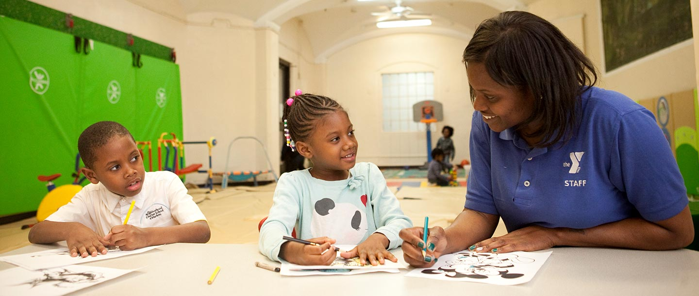 Woman coloring with two children at Harlem YMCA